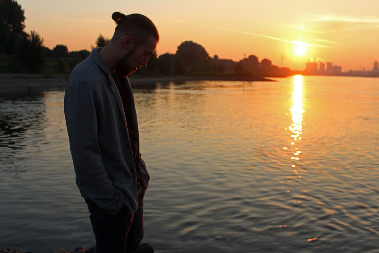 Side view of young man standing by lake against sky during sunset