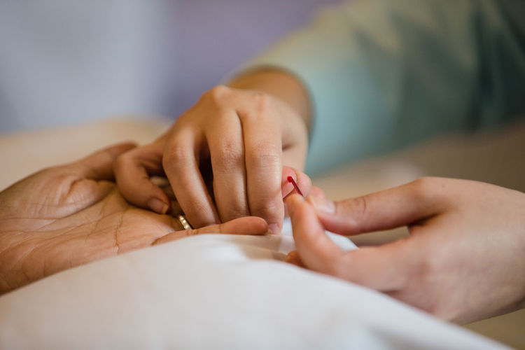 Close-up of nurse taking blood sugar test of patient