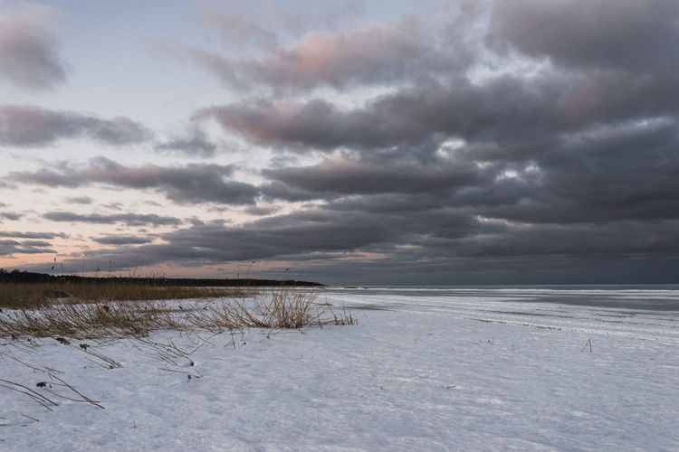 Scenic view of snow covered land and sea against sky