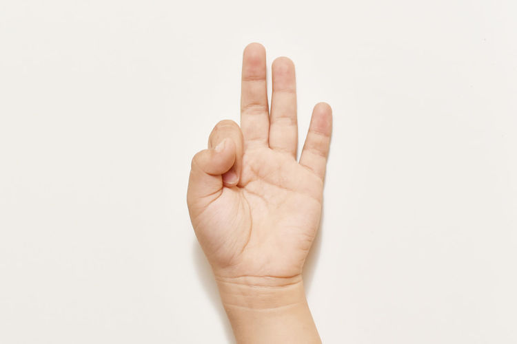 Cropped Image Of Person Showing Ok Sign Against White Background