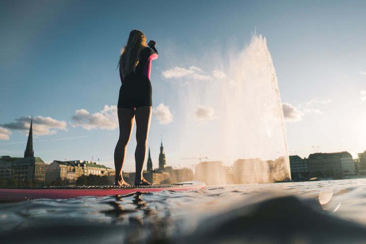 Full length of woman standing by sea in city against sky