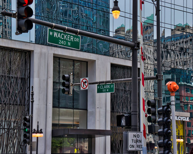 Chicago, IL / USA - 7/19/18: Busy intersection of Wacker Drive and Clark Street in downtown Chicago Loop. Caution Chicago Chicago Loop Downtown Chicago Sign Streetlamp Wacker Drive Architecture Building Exterior Built Structure Clark Street Day Editorial  Guidance Light No Right Turn No Turn On Red Outdoors Road Sign Road Signal Safety Sign Stoplight Stoplights Streetlight