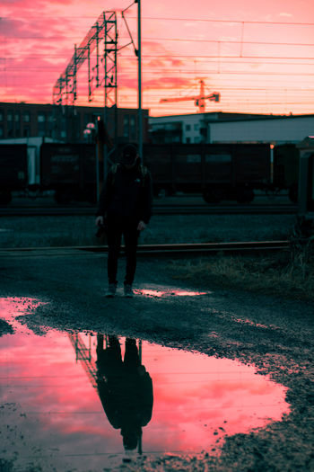 Man with umbrella walking on road against sky during sunset
