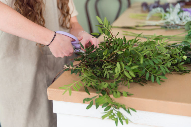 Midsection of florist cutting leaf stems at table