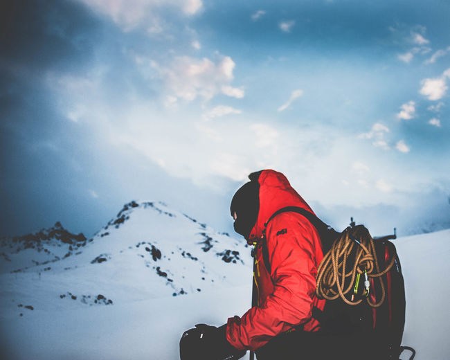 Side view of person standing on snowcapped mountain against cloudy sky