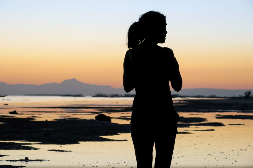 Woman silhouette on a rocky island beach at low tide Alone Backpacker Beach Sunset Depression Digital Nomad Girl Silhouette Holiday Trip Island Getaway Island Sunrise Island Sunset Island Vacation Island View  Lonely Lonely Girl Lonely Woman Sadness Silhouette Single Life  Single Woman Solo Traveller Solo Trip Tourist Woman World Travel World Traveller