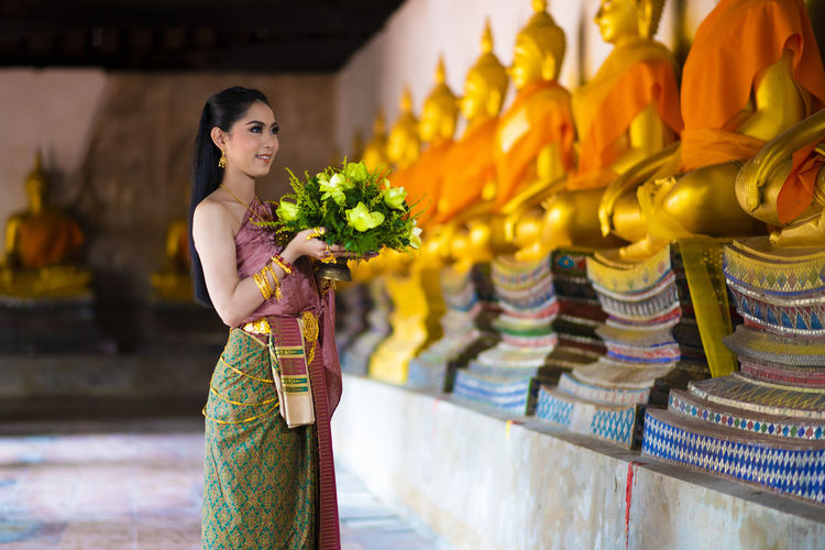 Woman holding flowers while standing by statues in temple