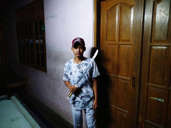 Portrait of boy standing against door