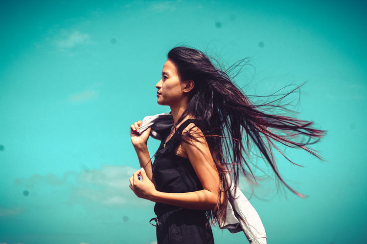 Young woman looking away while standing against blue sky
