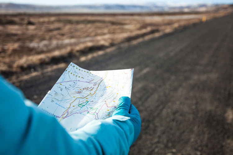 Midsection Of Person Holding Map On Road