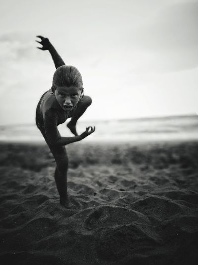 Portrait Of Shirtless Boy Screaming While Playing At Beach Against Sky
