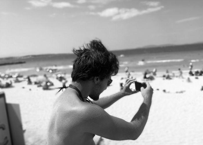Shirtless man photographing at beach against sky