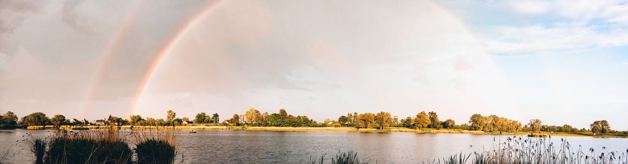 Panoramic view of lake against rainbow in sky