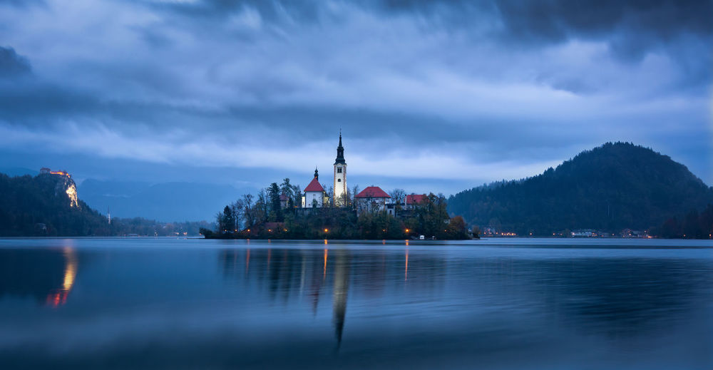 Dawn at lake bled in a cloudy day with island of the assumption of mary, mountains and bled castle