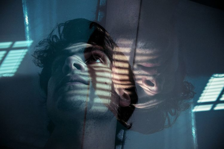 Double exposure image of thoughtful young man looking away
