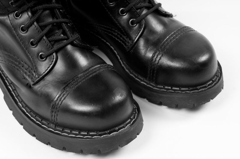Pair of black leather bovver boots detail on white background, horizontal orientation, nobody. Army Shoes Black Boot Boots Bovver Close-up Footgear Footwear Lace Laces Leather Menswear Military No People Pair Rubber Rugged Shoe Shoe Shoelace Shoes Steel-toe