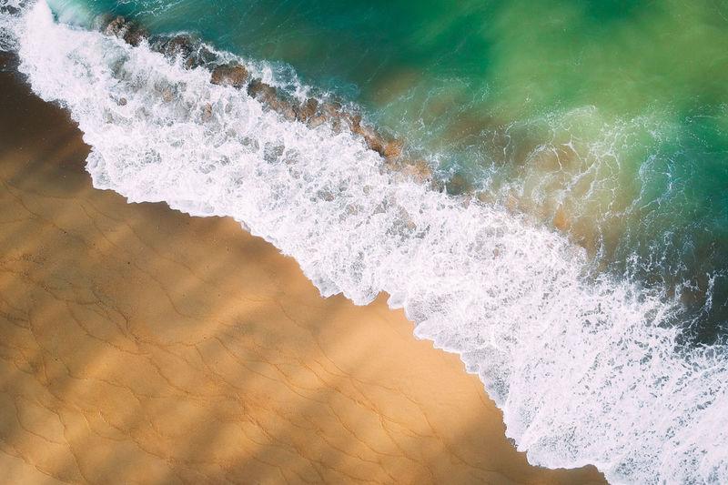 High angle view of waves rushing towards beach
