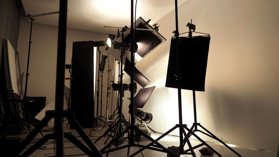 Lighting setup in studio for commercial works such as photo movie or video film production which use many LED light more than 1000 watts with big softbox snoot reflector umbrella and tripods. Arts Culture And Entertainment Behind The Scenes Camera - Photographic Equipment Communication Electric Lamp Equipment Film Industry Film Studio Filming Illuminated Lighting Equipment Man Made Man Made Object No People Photo Shoot Photographic Equipment Photography Themes Spotlight Stage Studio Studio; Photo; Equipment; Photography; Background; Professional; Photographer; Light; Camera; Empty; White; Creative; Modern; Lamp; Flash; Black; Fashion; Shot; Halogen; Photograph; Photographic; Technology; Nobody; Spotlight; Soft; Illuminated; Electrica Technology Wall - Building Feature