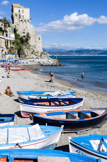 Cetara, Italy - October 2, 2013: Cetara small beach village on the Amalfi Coast, LA beach is defended by an ancient Saracen tower. Bathers on the beach on a warm October day. In the background you can see the city of Salerno Beauty In Nature Blue Boat Cloud Cloud - Sky Coastline Day Mode Of Transport Mountain Nature Nautical Vessel No People Outdoors Scenics Sea Shore Sky Tourism Tranquil Scene Tranquility Travel Destinations Vacations Water