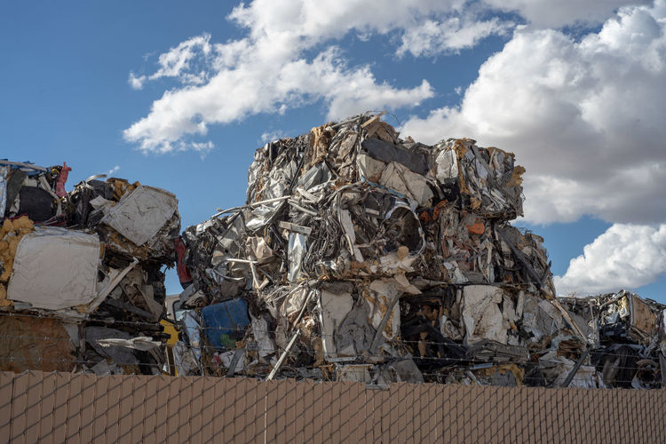 Stack of garbage on metal against sky