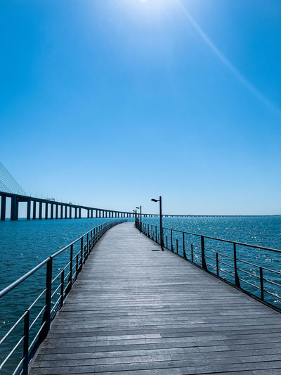 Blue on blue  sky and water with curving pier and bridges into the distance on bright sunny day