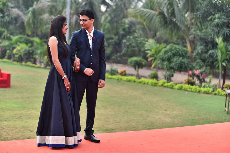 Full length of bride and bridegroom standing at park lawn during wedding ceremony