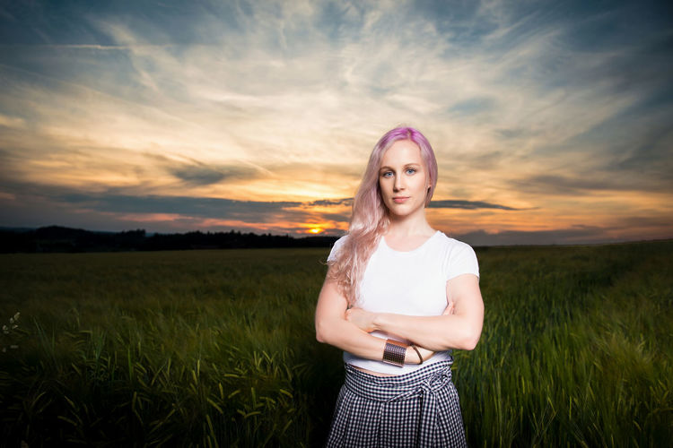 Beautiful young woman standing on field at sunset