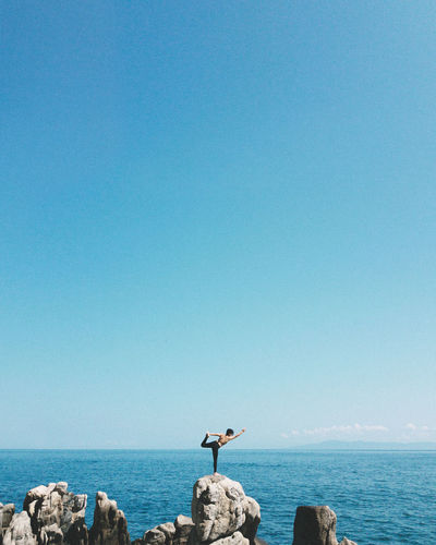 Mid distance view of woman practicing yoga while standing on rocks against sea and sky