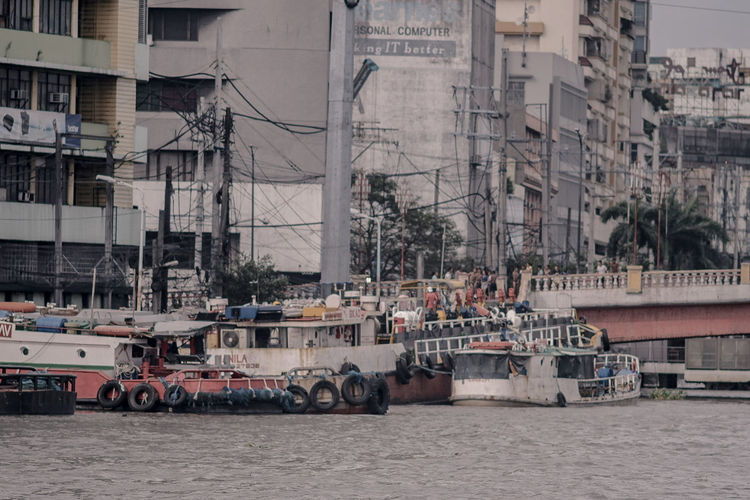 Boats in river by buildings in city