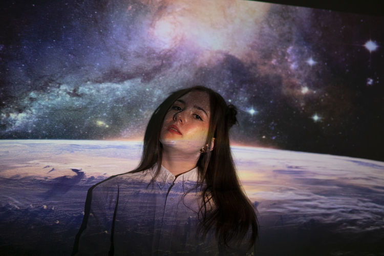 Portrait of young woman against sky at night
