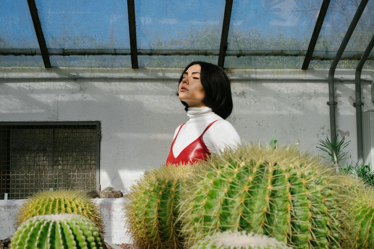 Young Woman Standing By Cactus In Greenhouse