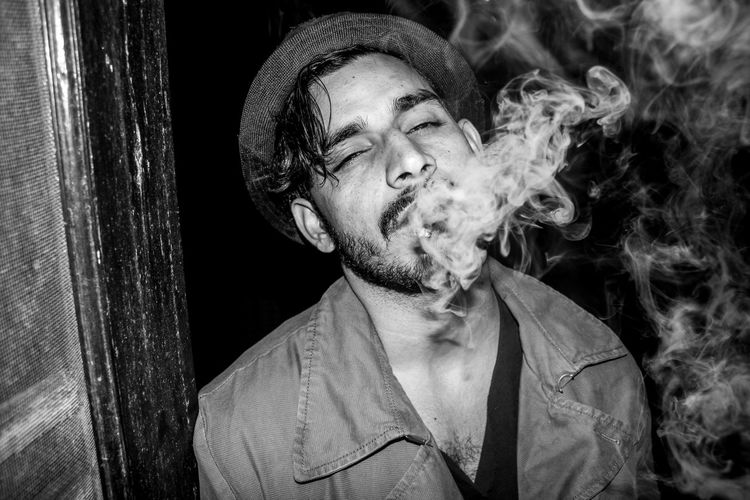 Portrait of man smoking while standing outdoors