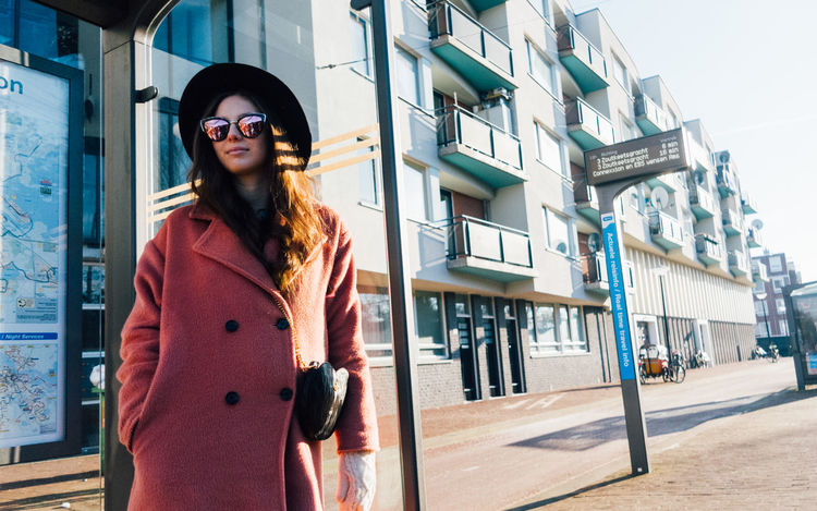 Waiting for a tram in Amsterdam. Alicia Scammell Amsterdam Beautiful Woman Building Exterior City Cold Cold Temperature Day Fashion Fashion Photography Lifestyles One Person One Woman Only One Young Woman Only Only Women Outdoors Shades Standing Sunglasses Tram Waiting Waiting For The Bus Women Young Adult