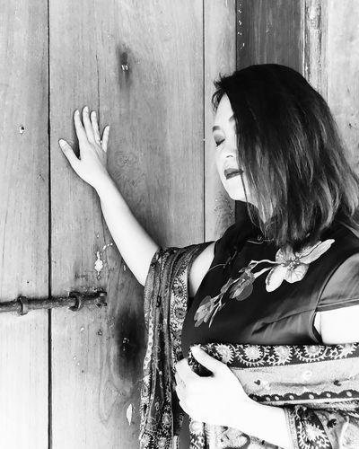 Beautiful woman standing by wooden door