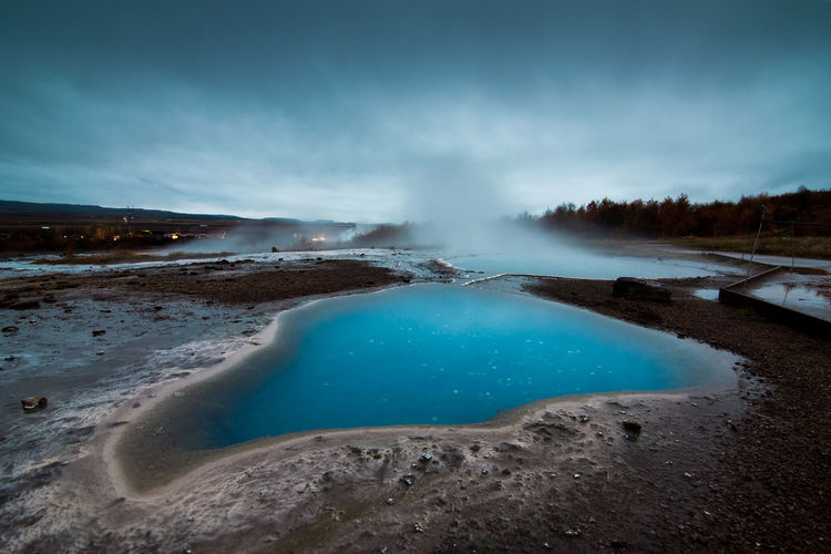 Scenic View Of Hot Springs Against Cloudy Sky