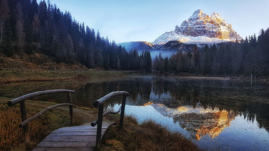 Reflection of snowcapped mountain in lake at forest