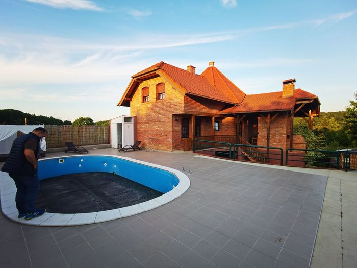 Man relaxing in swimming pool by building against sky