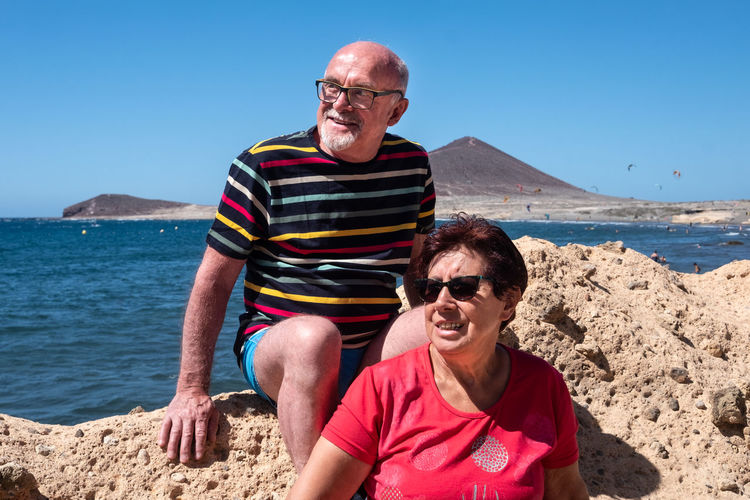 Smiling senior couple sitting on rock by sea