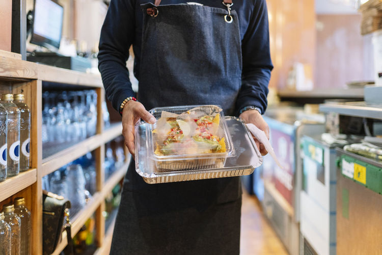Midsection of man holding ice cream at store
