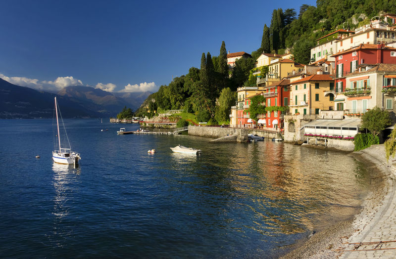 Boats on lake como by buildings against sky