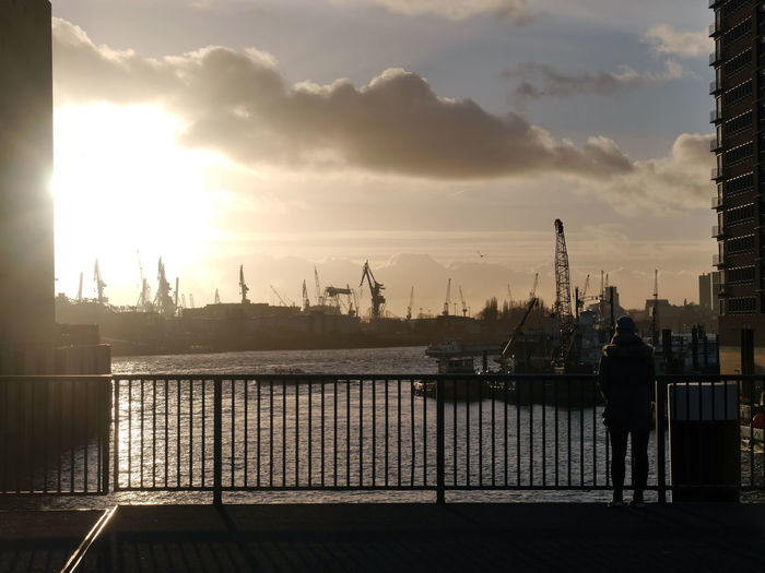Rear view of woman standing at harbor against cloudy sky