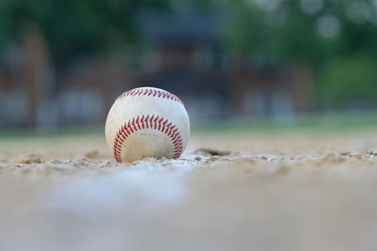 A baseball sits on a ball field right on the foul line between home and first base Baseball Baseball Game Field Activity Ball Ball Stitches Baseball - Ball Baseball - Sport Chalk Lines Dirt Foul Ball Healthy Healthy Eating Horizonrtal Image Little League Baseball Outdoors Playing Field Red Thread Sand Selective Focus Sport Sports Sports Life  Stitching