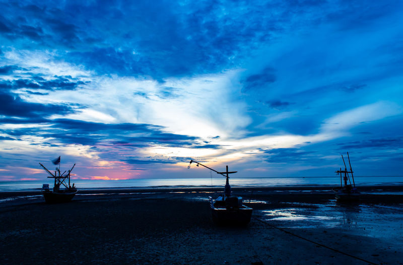The morning sun light in the sea, and the boat on the beach. Beauty In Nature Cloud - Sky Construction Equipment Dusk Industry Land Machinery Mode Of Transportation Nature Nautical Vessel No People Outdoors Scenics - Nature Sea Silhouette Sky Sunset Transportation Water