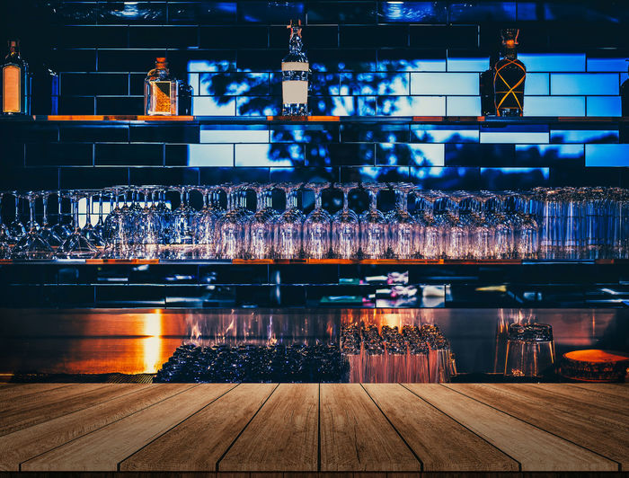 Wooden table in front of abstract blurred restaurant lights background of bar