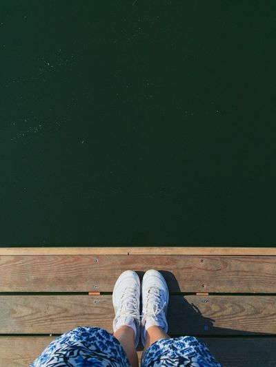 Low section of woman standing on jetty over lake