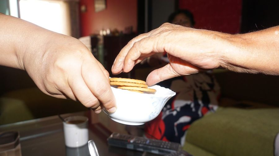 People sharing biscuits at home