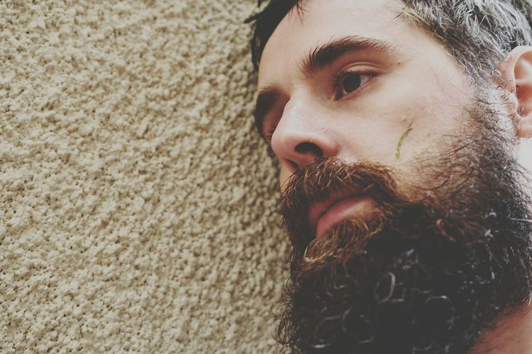 Close-up of bearded tensed man leaning on wall