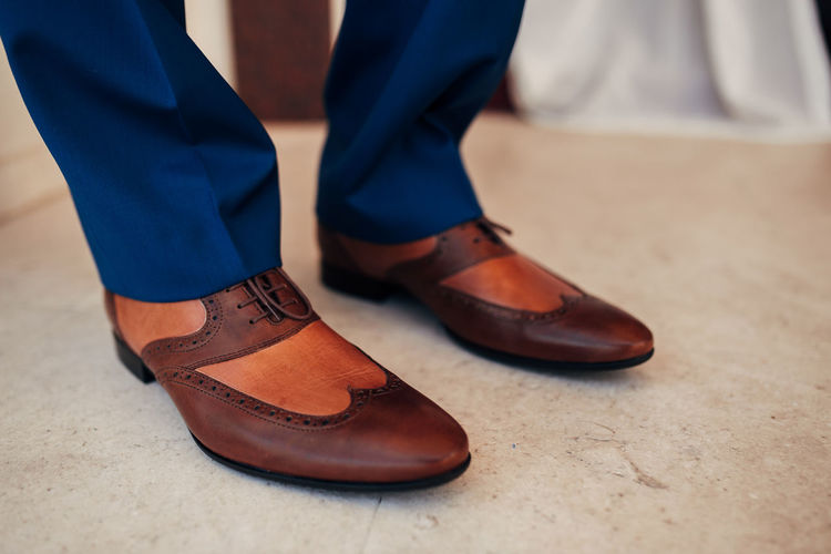 Low section of person wearing shoes standing on tiled floor