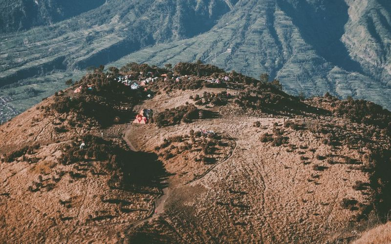 High angle view of people on savanna against mountains