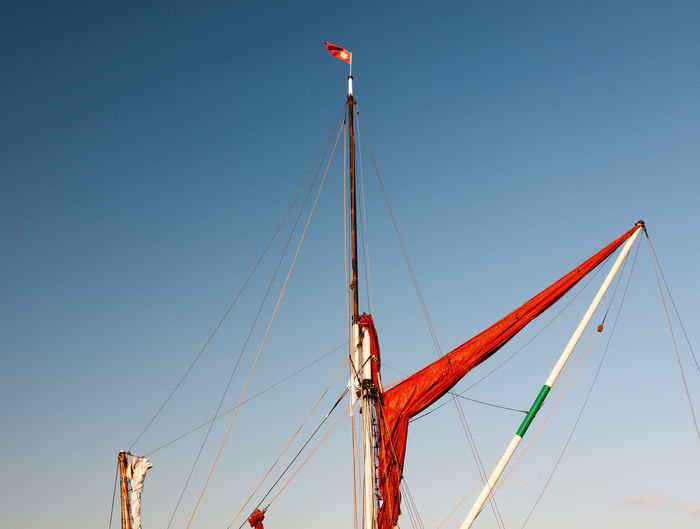 Low angle view of flag hanging on mast against clear blue sky